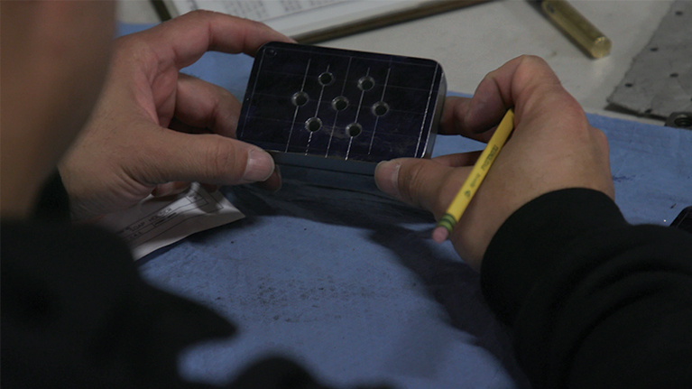 A piece of metal with holes in it being examined by a student
