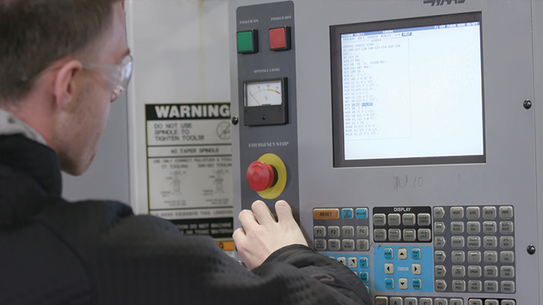 Male student programming the CNC Machine
